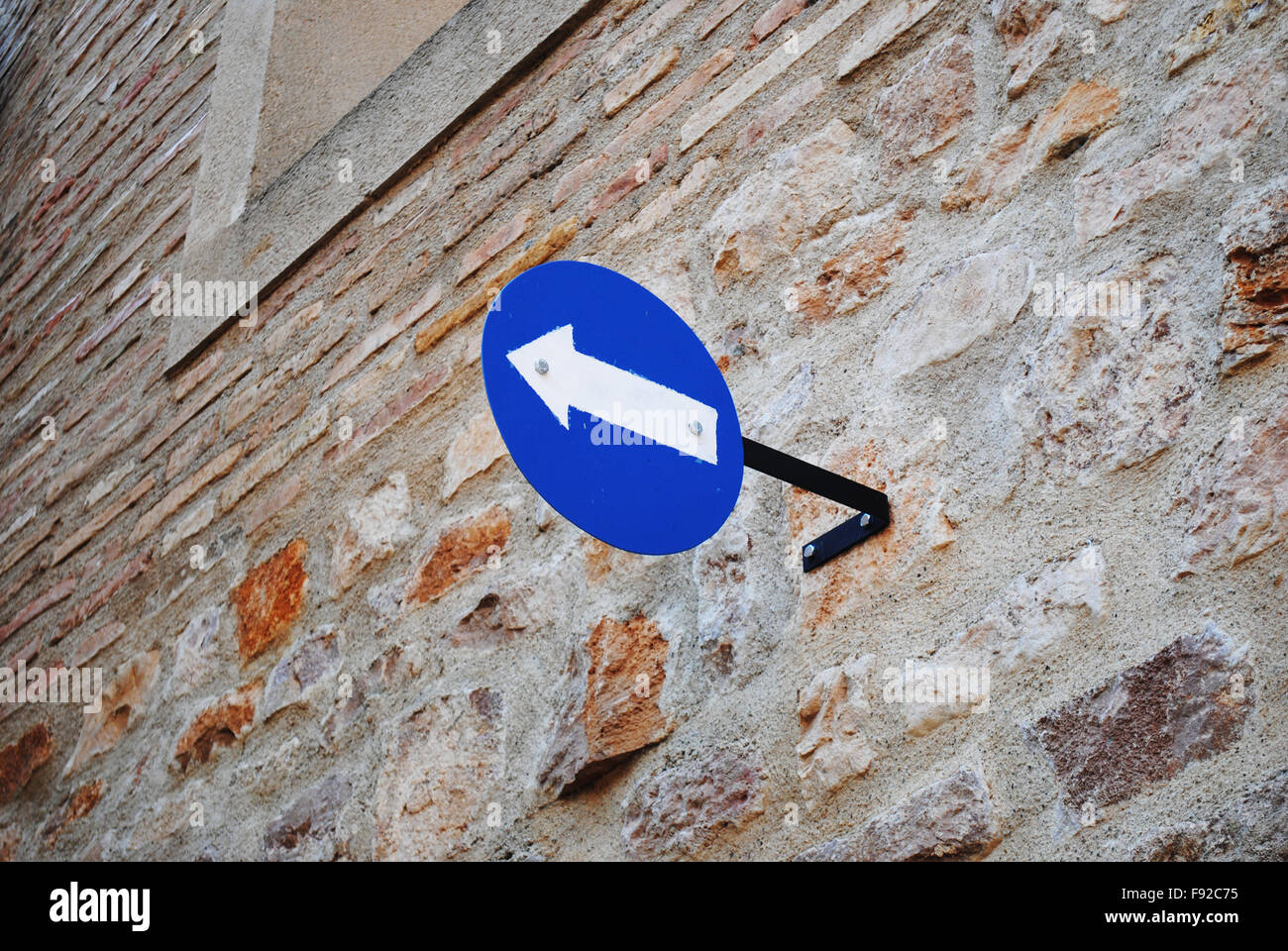 A left turn sign attached to a brick wall. - Stock Image