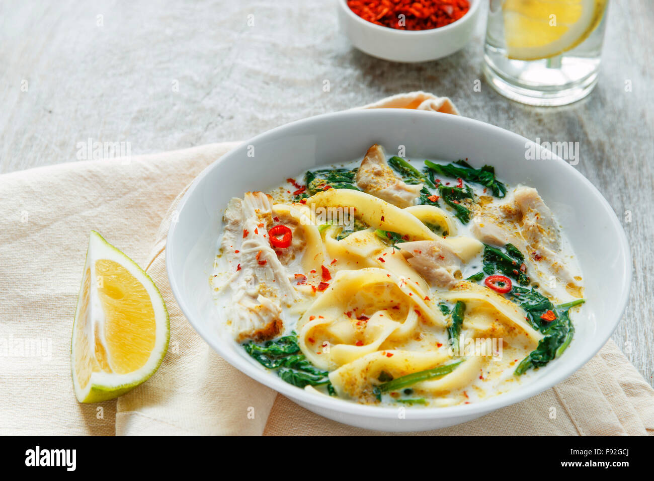 Coconut Curry Chicken Soup with noodles in a plate - Stock Image