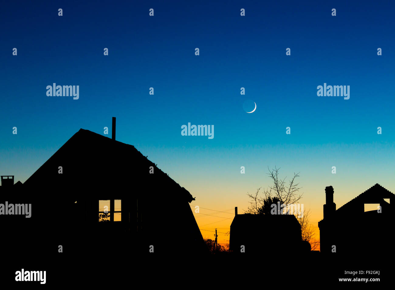 Roofs silhouettes against the night sky with new moon - Stock Image