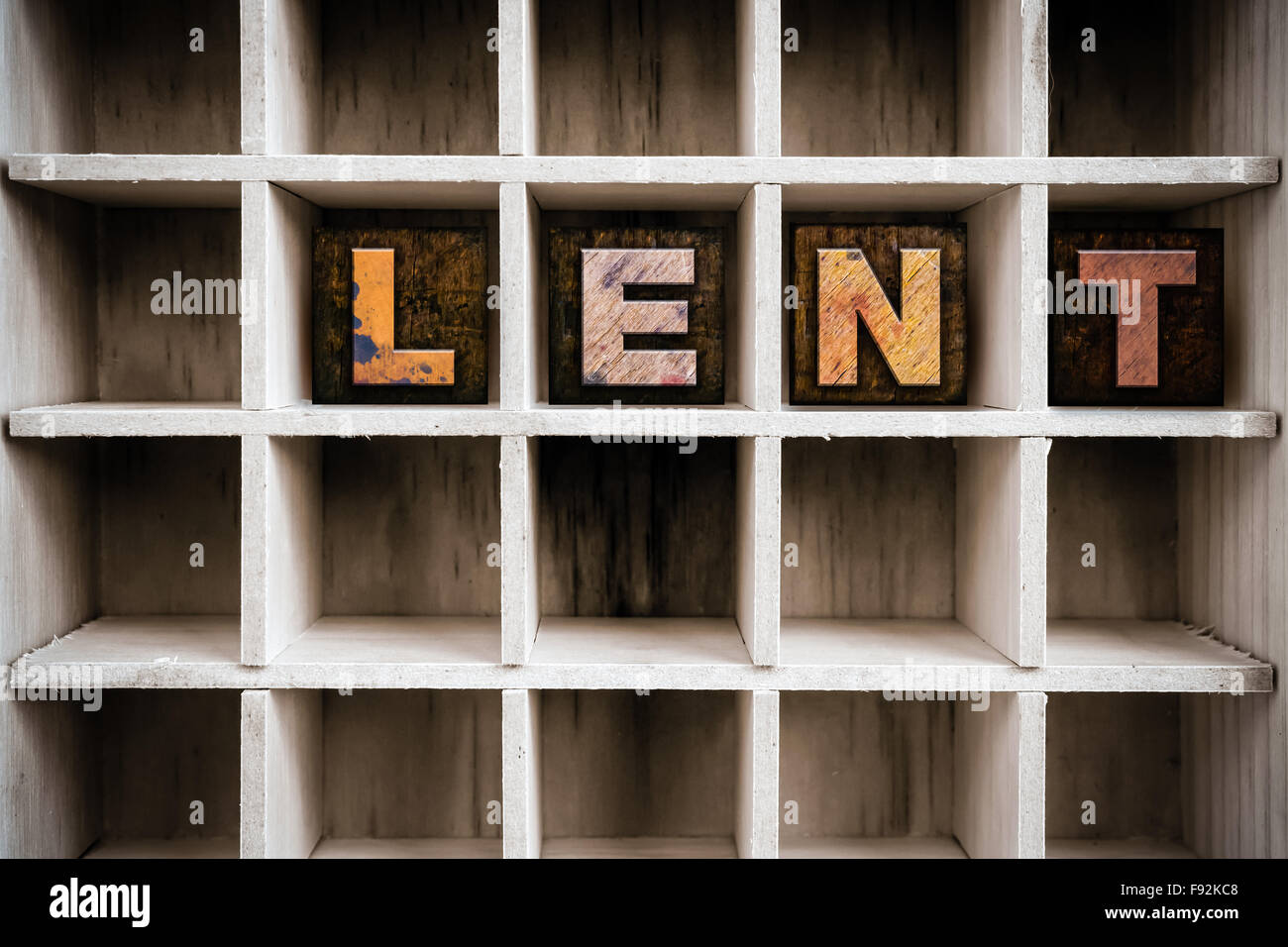 """The word """"LENT"""" written in vintage ink stained wooden letterpress type in a partitioned printer's drawer. Stock Photo"""