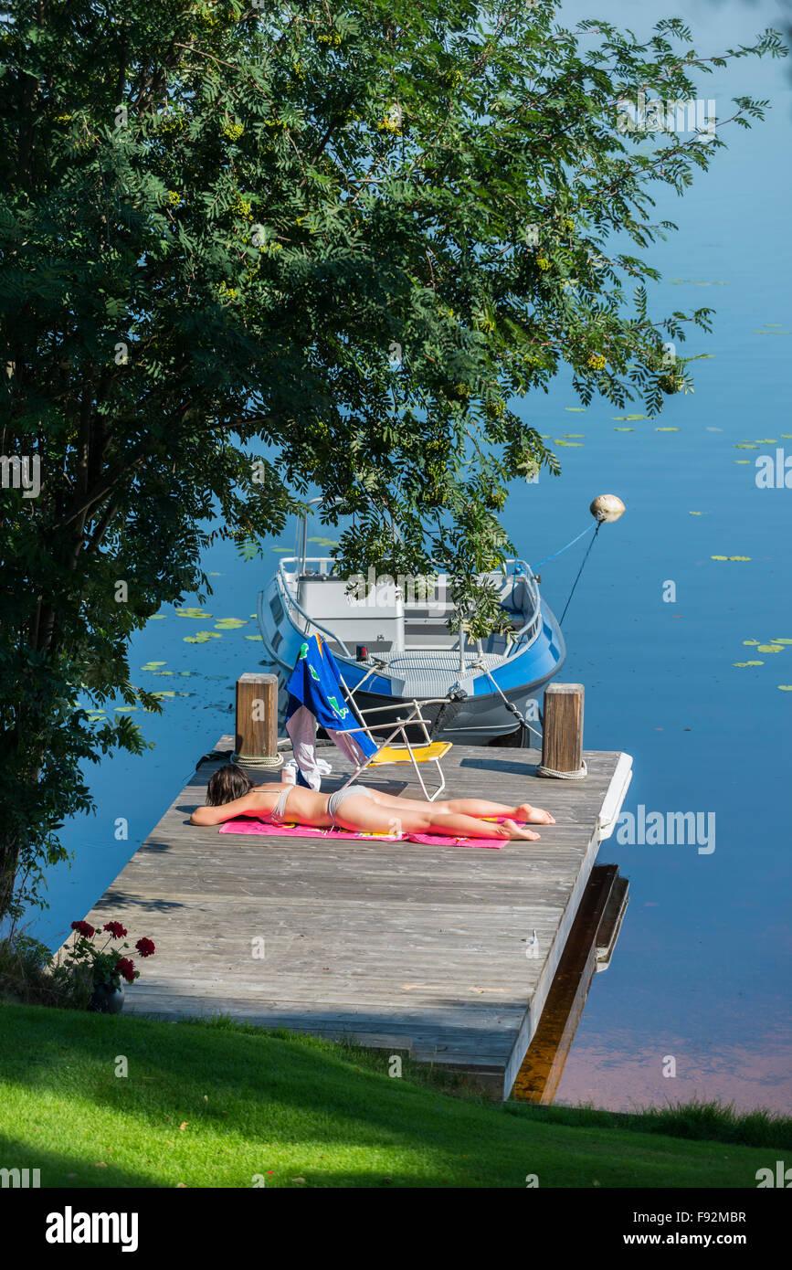 Sunbath on jetty - Stock Image