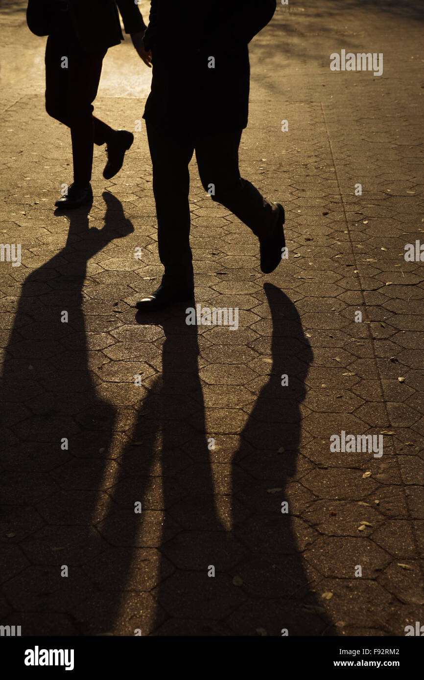 Abstract background of people's legs walking at night in streetlight - Stock Image