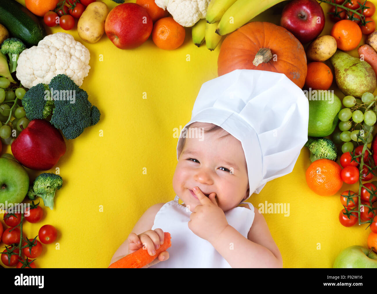 Baby surrounded by fruits and vegetables - Stock Image