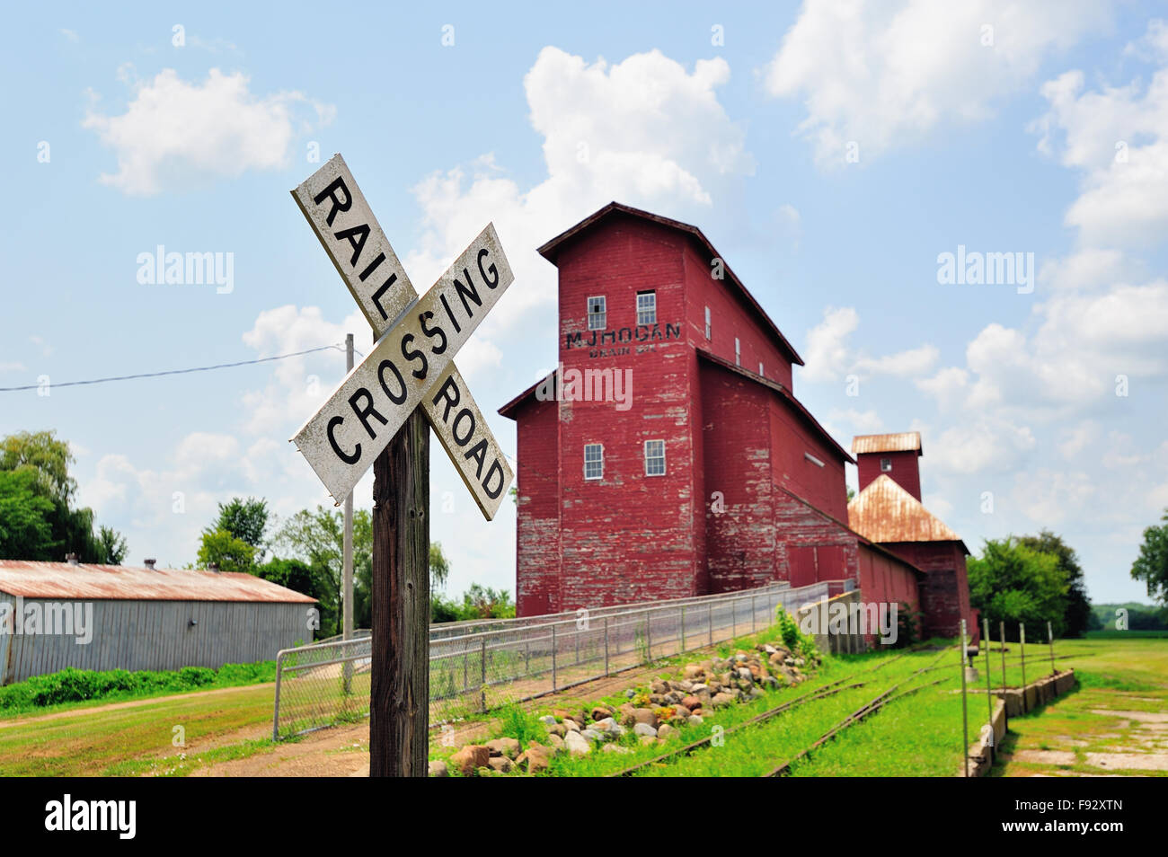 A vintage railroad crossing warning sign matches the age and appearance of the venerable grain elevator at a railroad - Stock Image