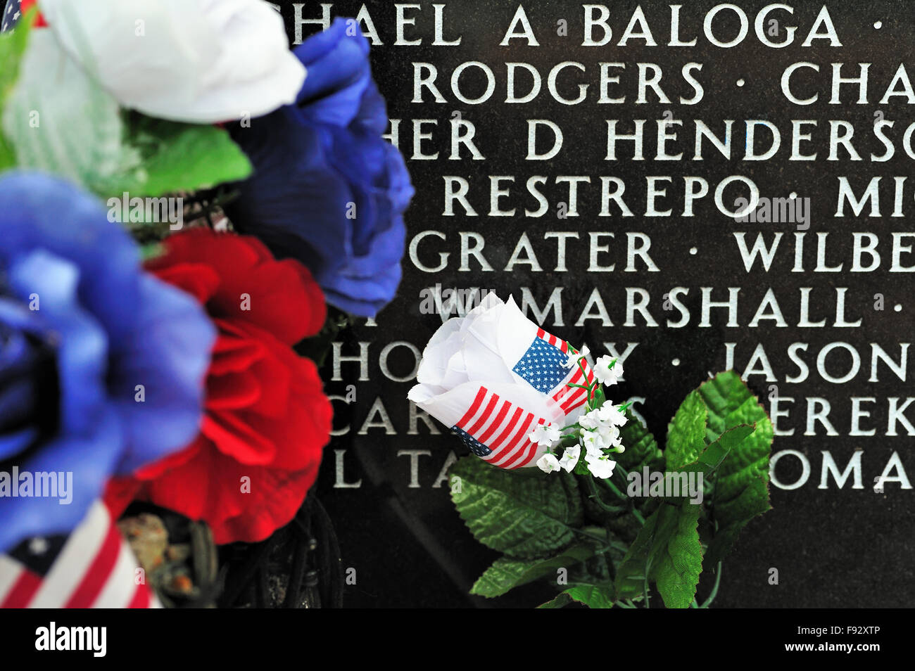 A close up of flowers left near one of the granite memorials at the Middle East Conflicts Wall Memorial in Marseilles, - Stock Image