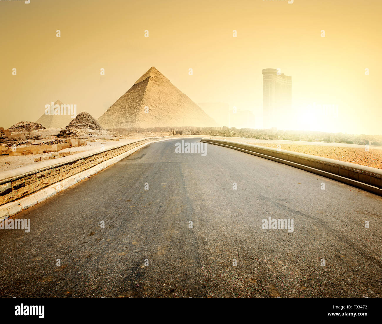 Asphalted road to pyramids and modern buildings of Giza - Stock Image