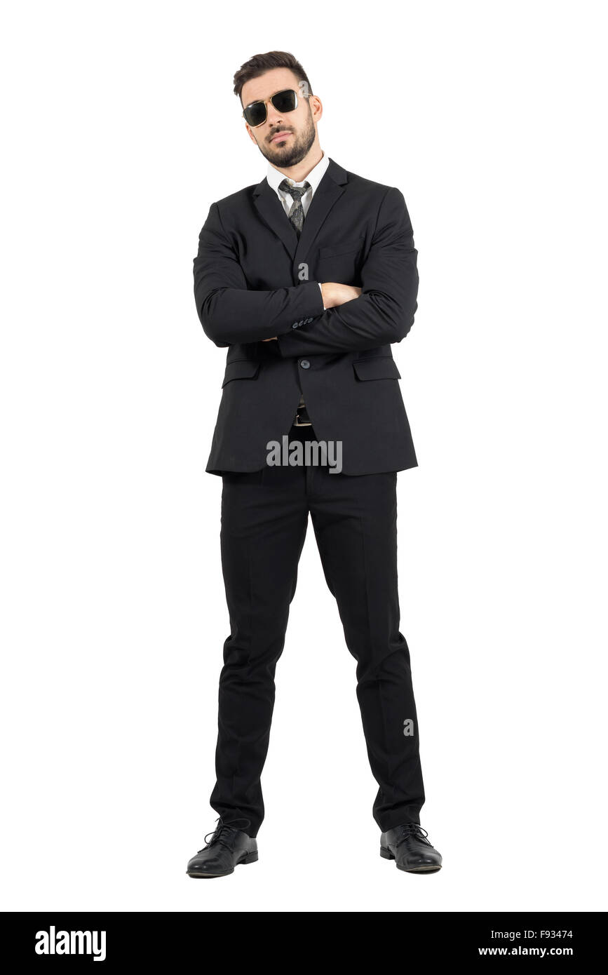 Secret agent or bodyguard with crossed arms looking at camera. Full body length portrait isolated over white studio - Stock Image