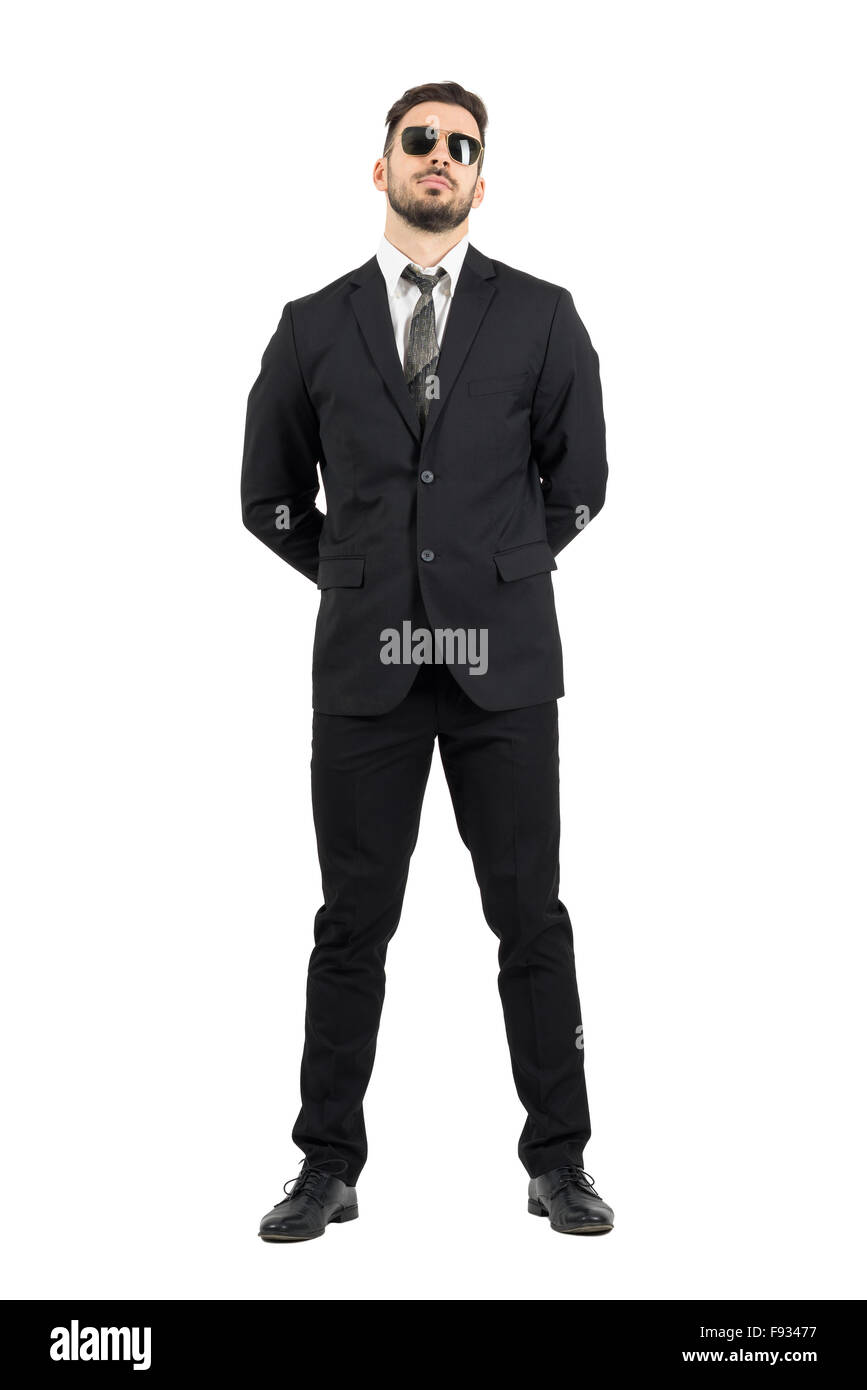 Secret agent or guard with hands behind back wearing sunglasses.Full body length portrait isolated over white studio - Stock Image