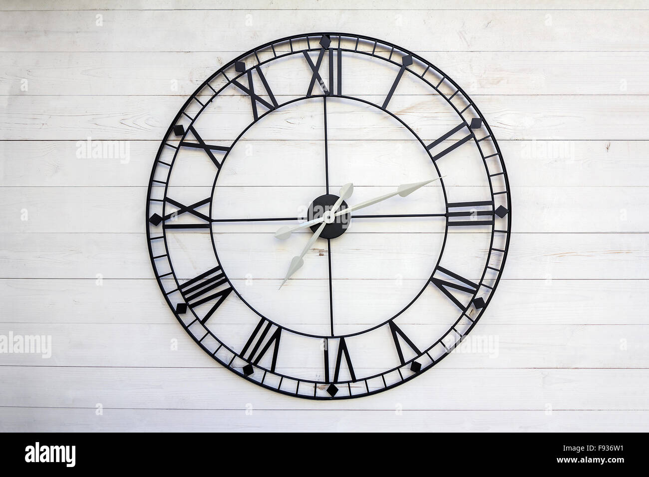 Old roman numeral clock on a wooden background - Stock Image