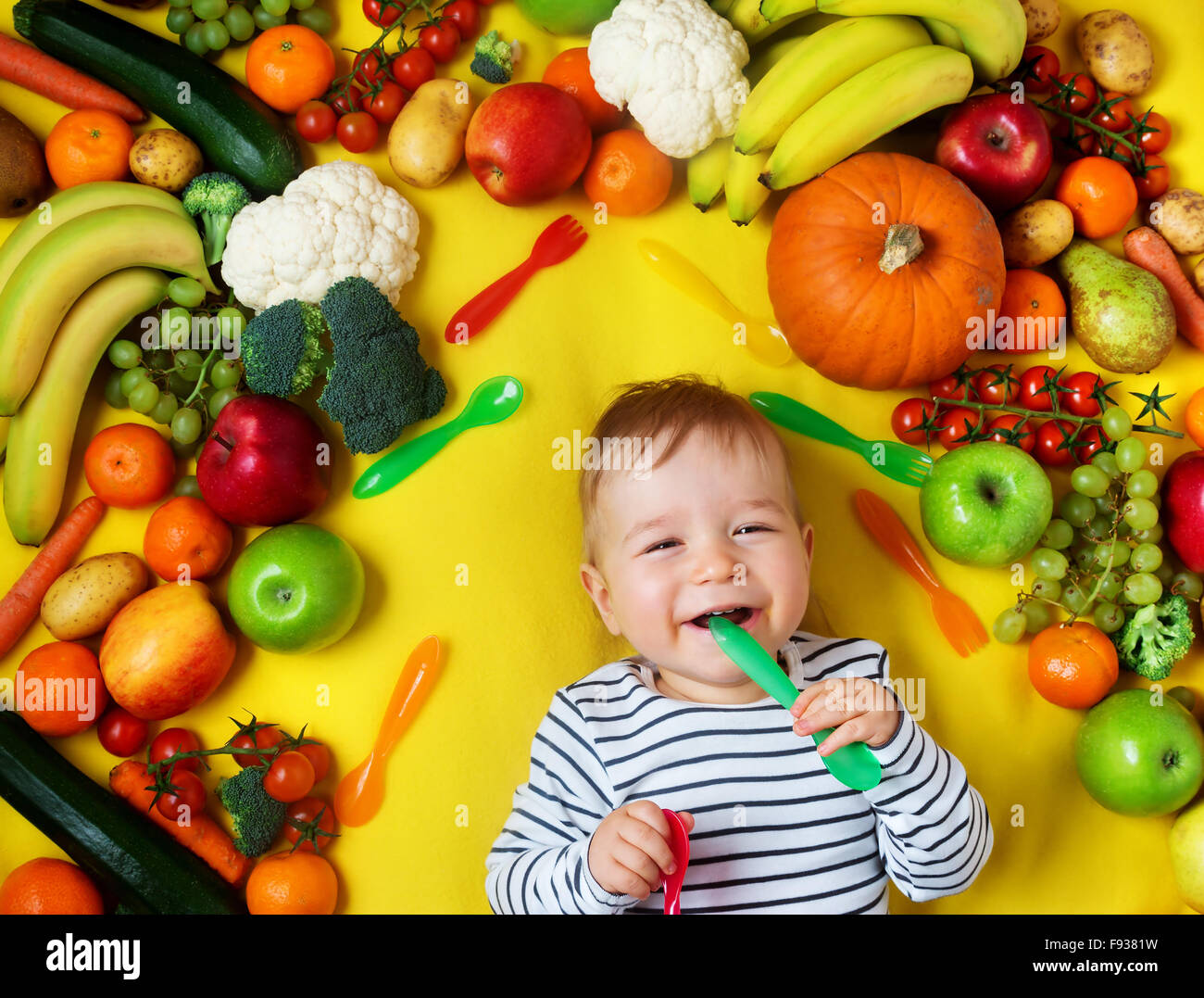Baby surrounded with fruits and vegetables - Stock Image