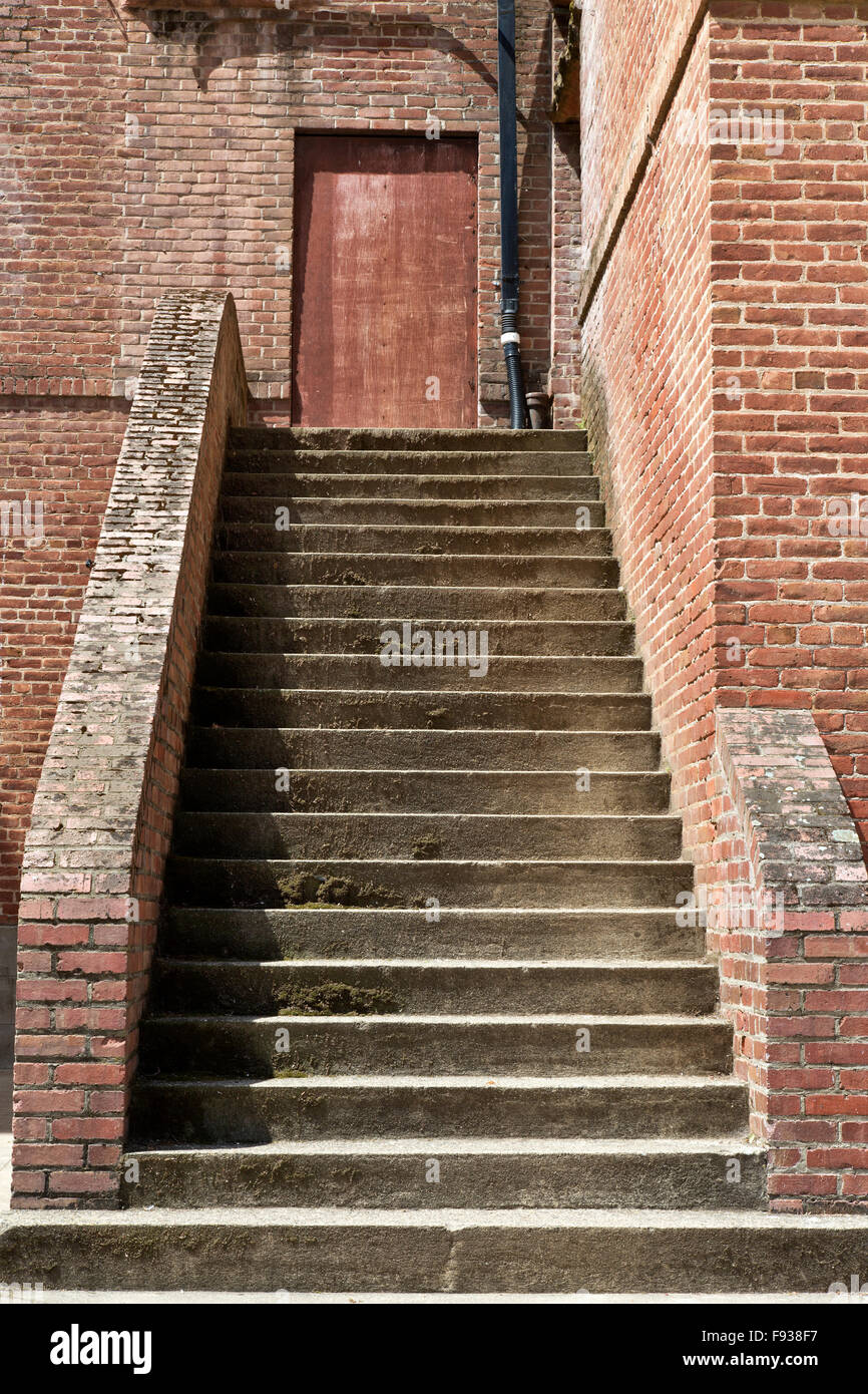 Stairs leading upward to a blocked doorway. - Stock Image