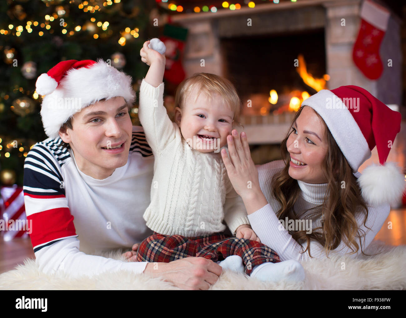 Happy family with child son lying near Christmas tree and fireplace  in living room - Stock Image