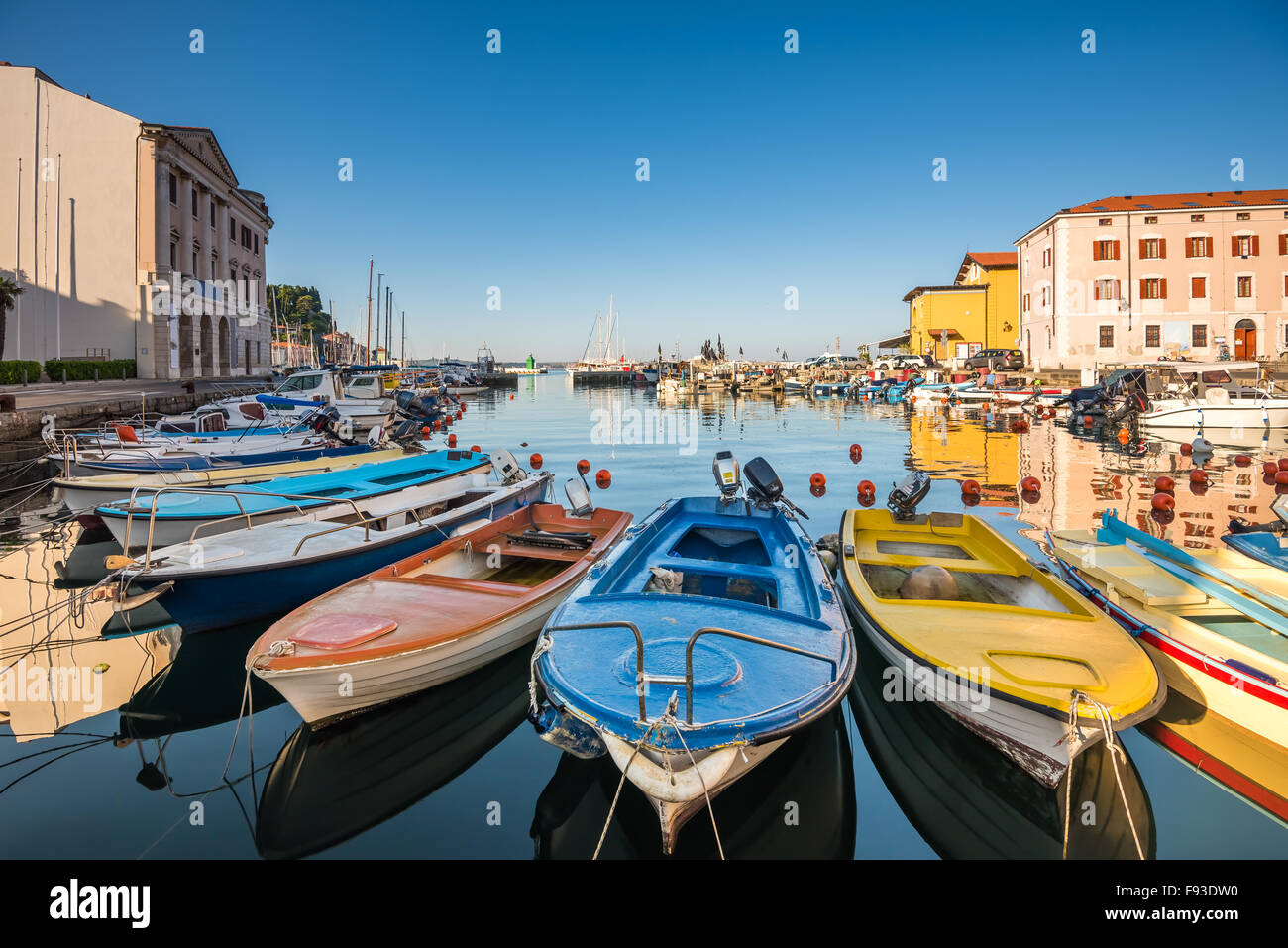 View of the Venetian Port of Piran, Slovenia with Boats in Foreground and Clear Blue Sky - Stock Image