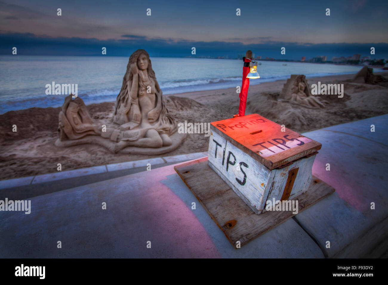 A makeshift box requests tips from passerbys for sand sculptures in Puerto Vallarta, Mexico. - Stock Image