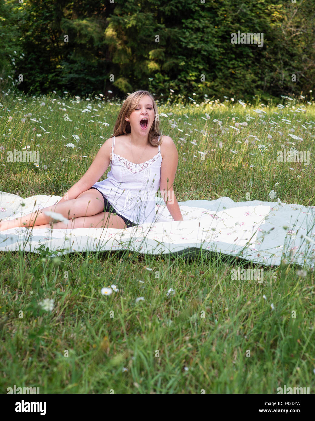 A young woman yawning in a field of flowers. - Stock Image