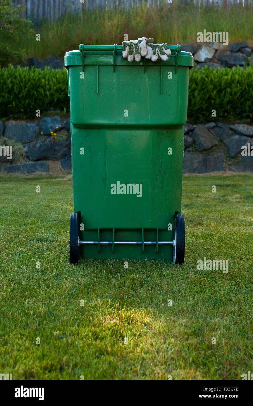 Yard work clean up and mowing with recycling bin - Stock Image