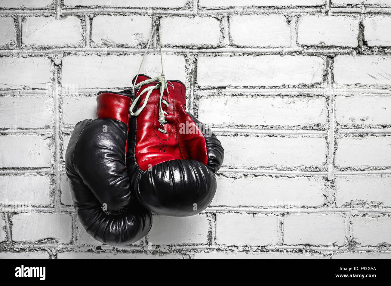 A pair of old boxing gloves hanging against a white brick wall. - Stock Image