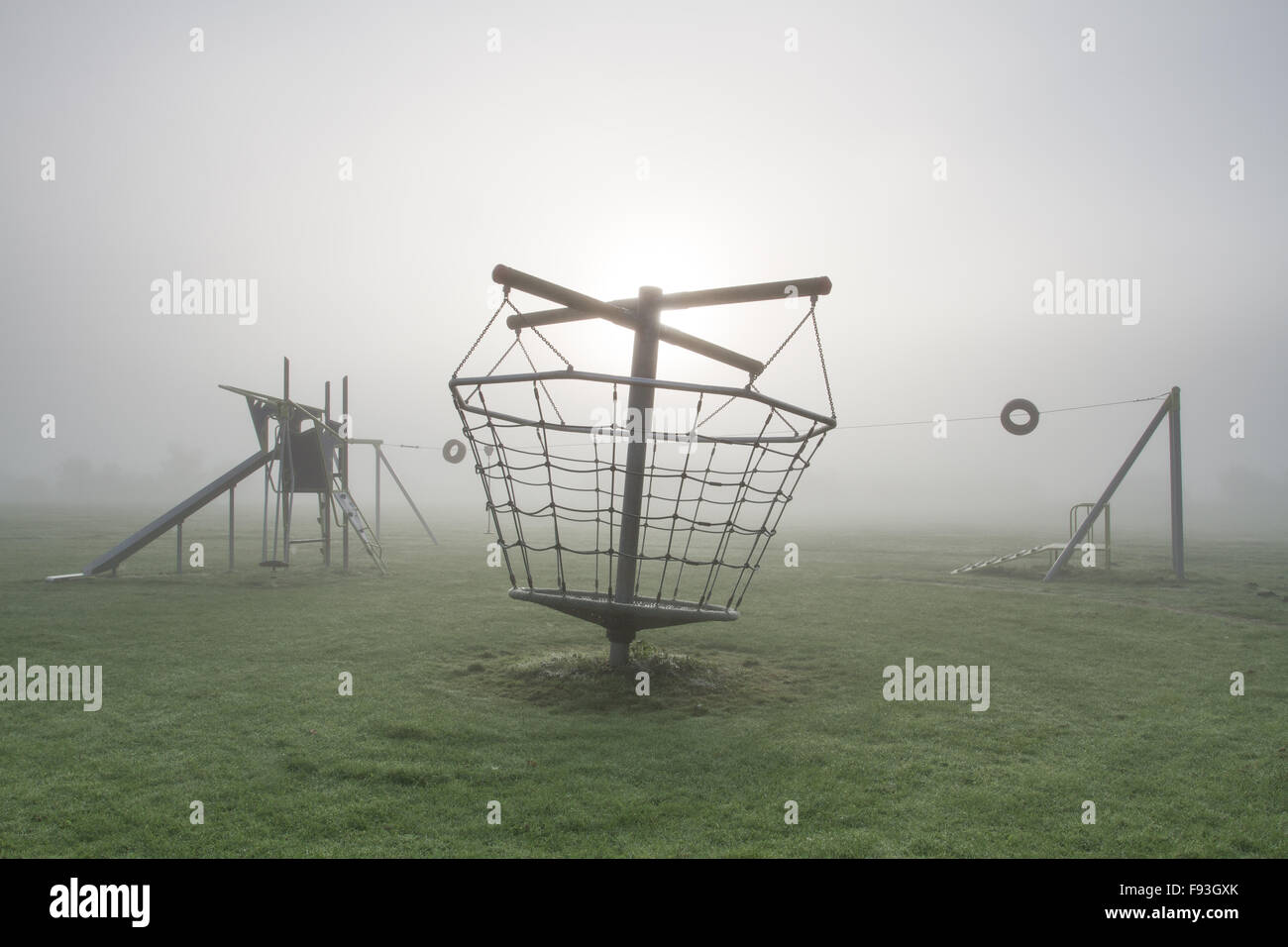 A deserted children's playground on a cold and foggy morning. - Stock Image