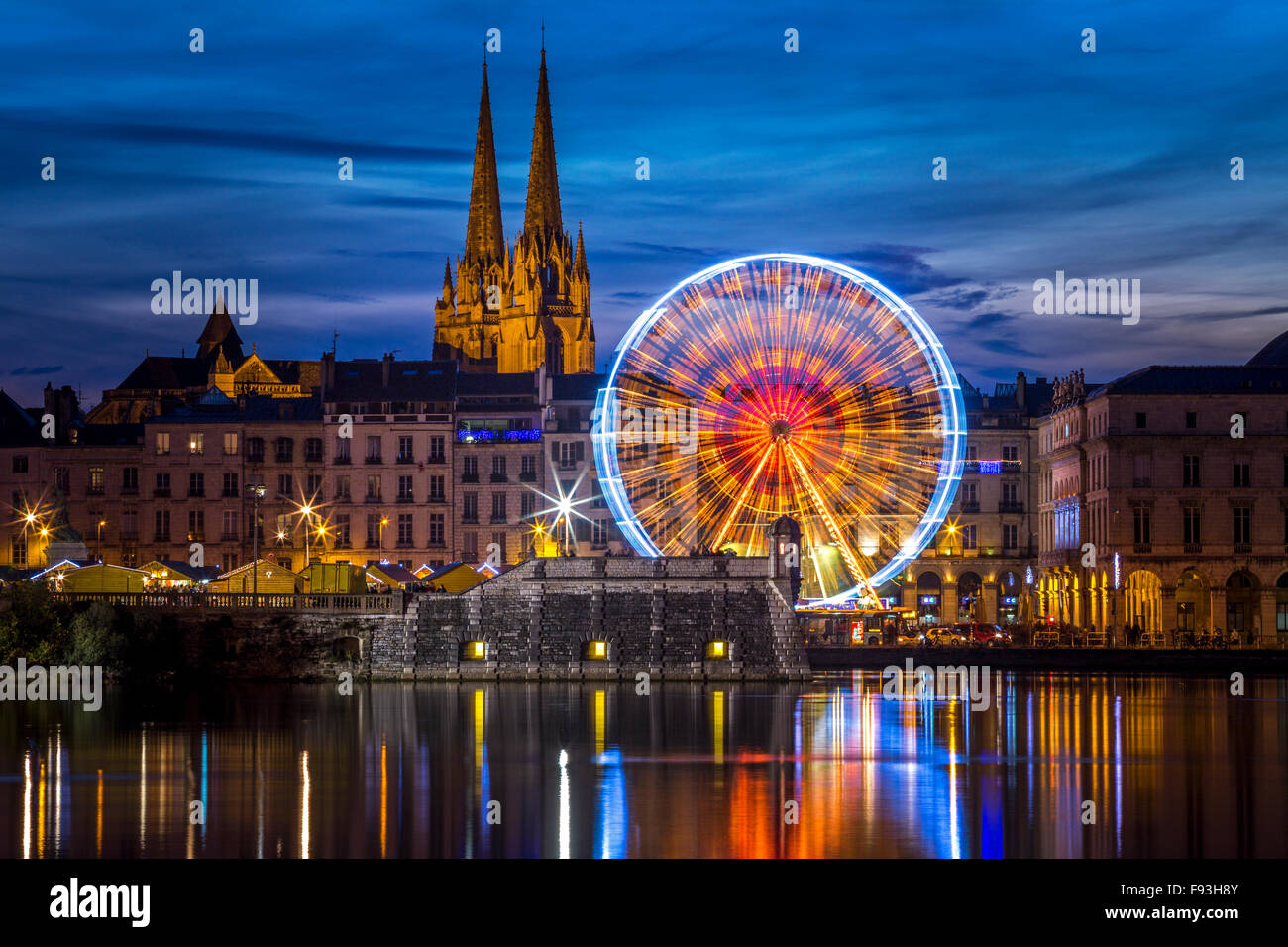 At night, a big wheel (Ferris Wheel) mirroring in water at the Adour and Nive river confluence (Bayonne - Aquitaine - Stock Image