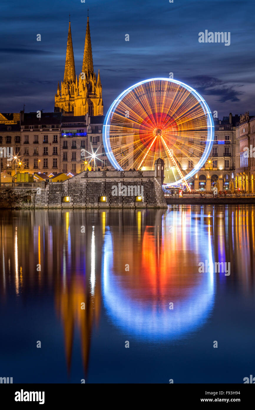 At night, a big wheel (Ferris Wheel) reflecting in water at the Adour and Nive river confluence (Bayonne - Aquitaine - Stock Image