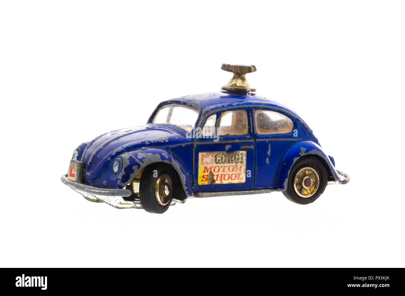 An Old Well Worn Corgi Motor School VW Beetle Die cast model on a white background. - Stock Image