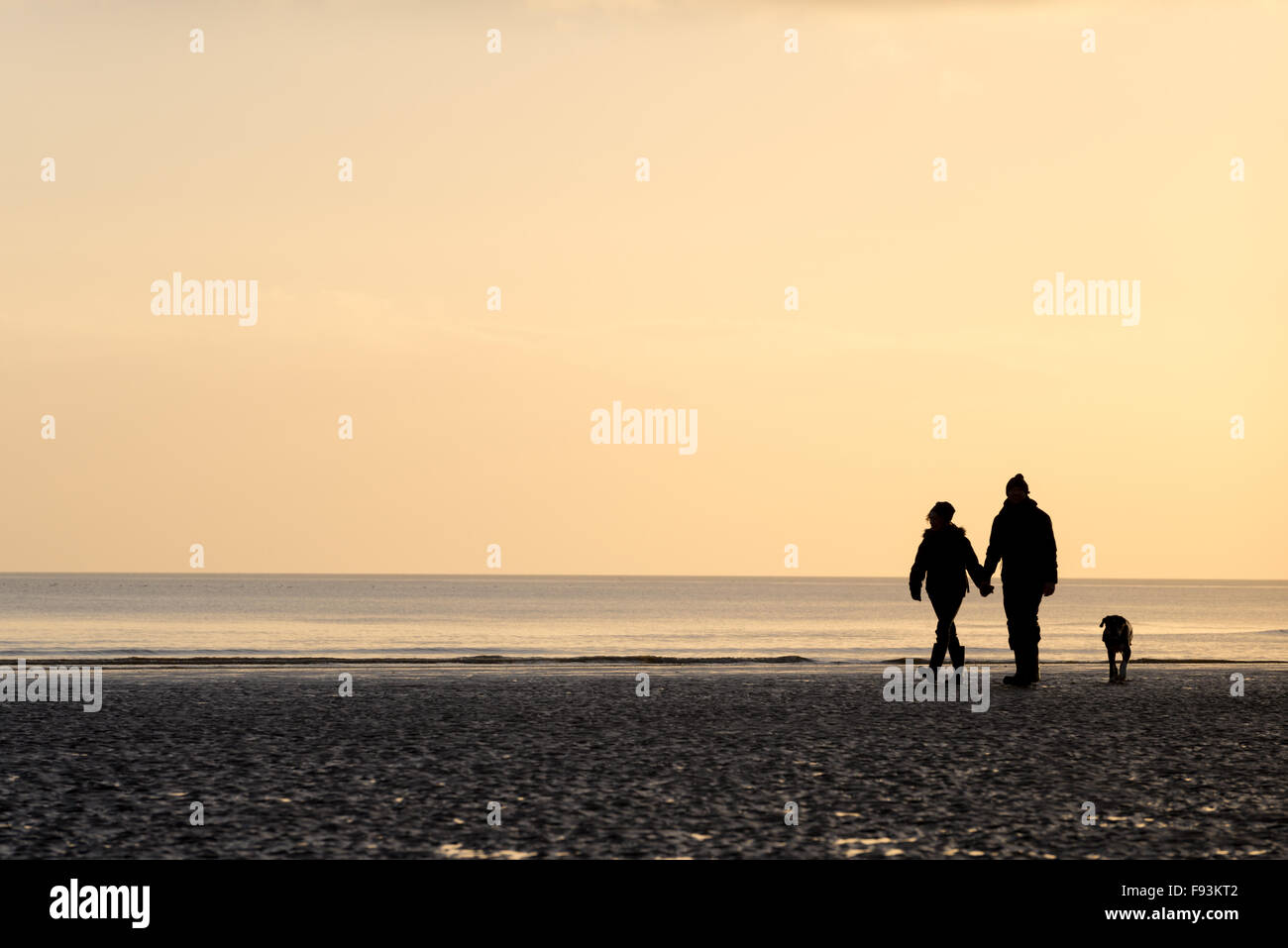 A couple walking their dog and holding hands on Camber beach, East Sussex. - Stock Image