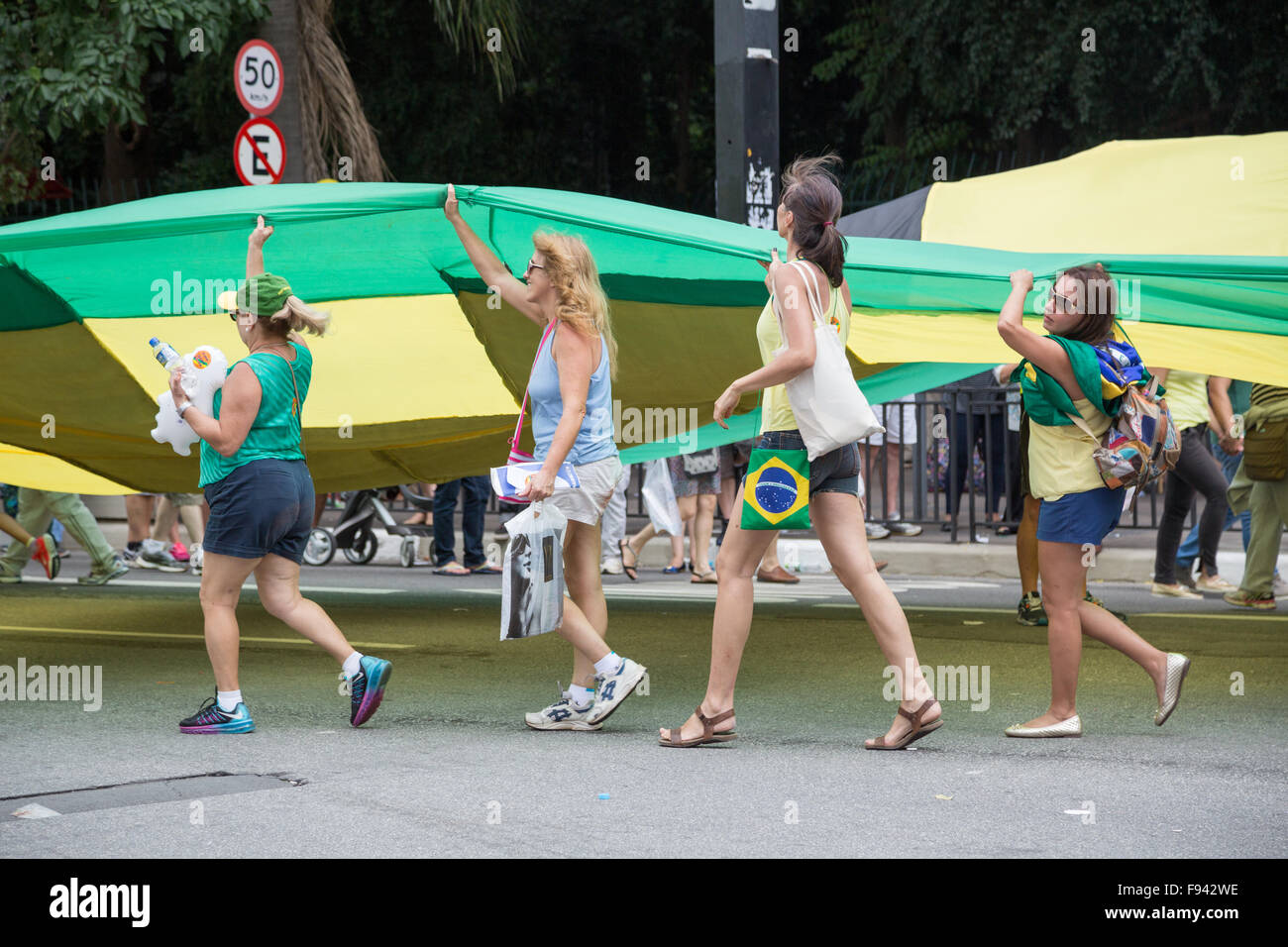 Sao Paulo, Brazil. 13th December, 2015. Demonstrators march holding a giant flag with the word 'Impeachment' - Stock Image