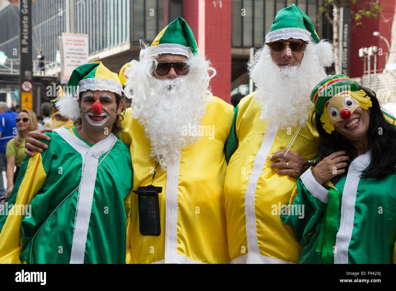 Sao Paulo, Brazil. 13th December, 2015. Demonstrators costumed clowns and Santa Claus with Brazil flag colors are - Stock Image
