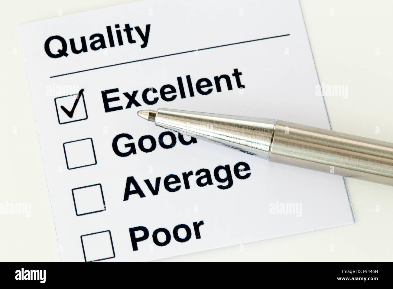 Ball pen setting a tick mark at excellent on quality checklist illustration - Stock Image