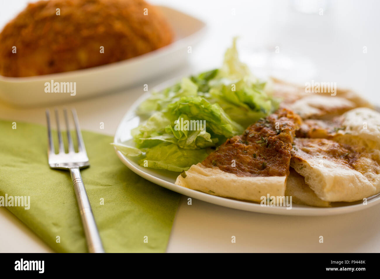 Indian curry naan bread on a plate with salad - Stock Image