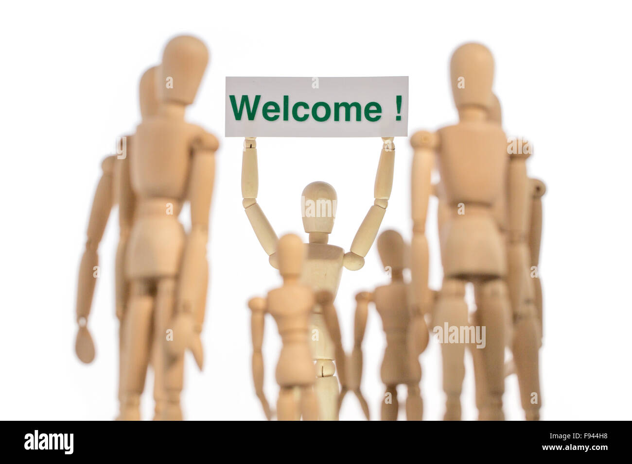 Warm welcome group of people with kids and adults staged with puppets on white background - Stock Image
