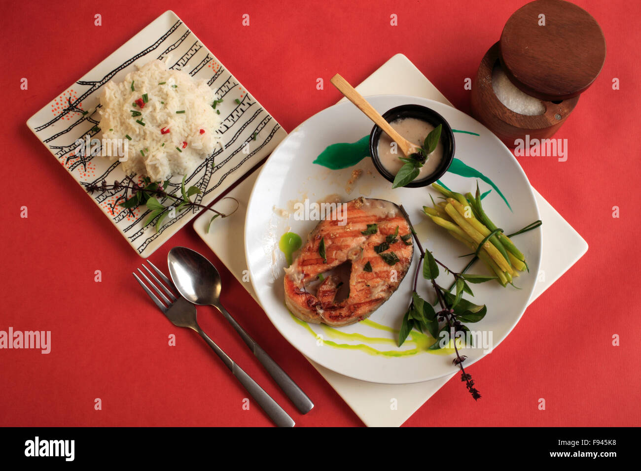 Grilled salmon steak, ginger & basil flower coconut infused sauce, rice, - Stock Image