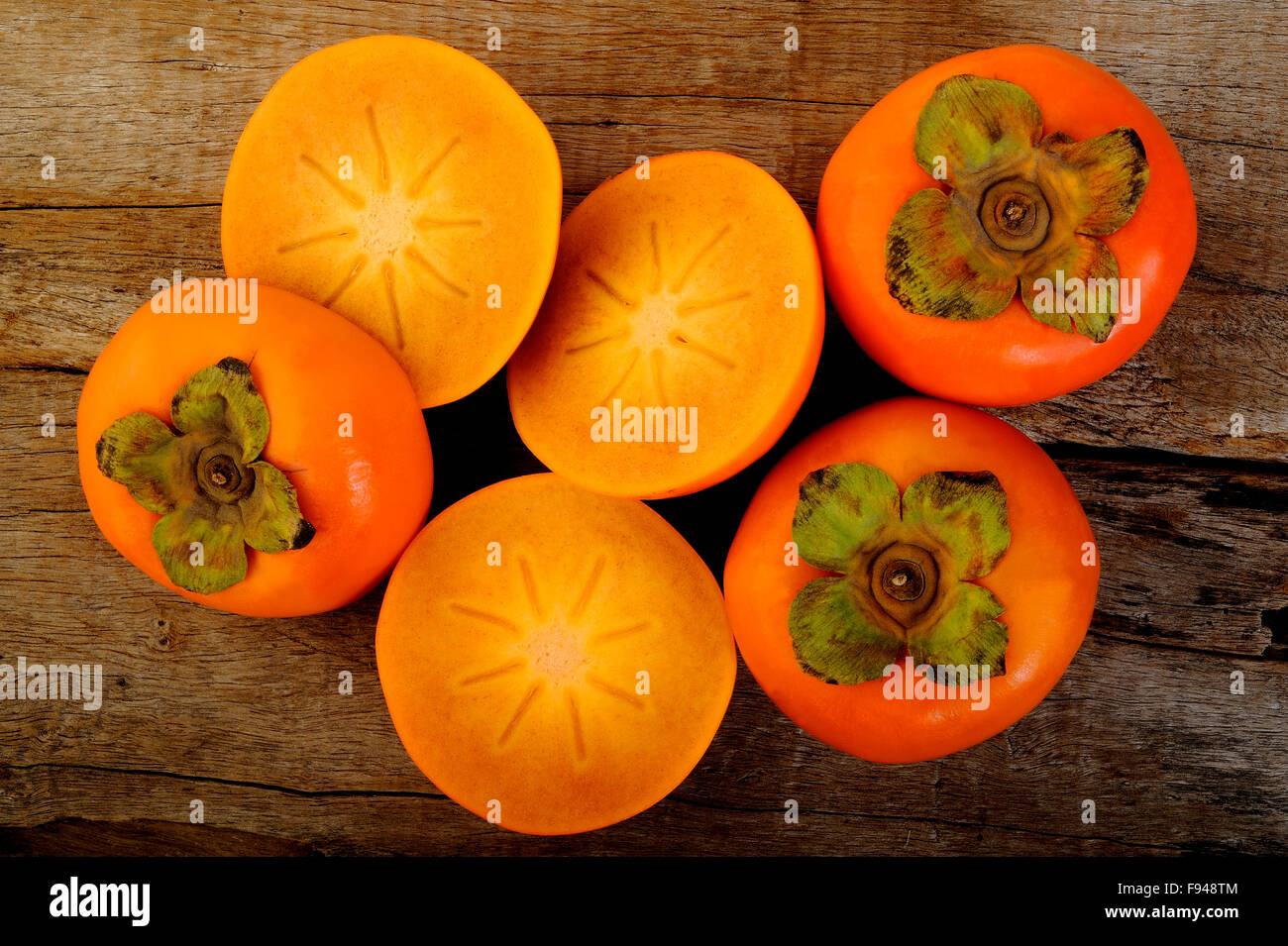 slice persimmon fruit on wooden background - Stock Image
