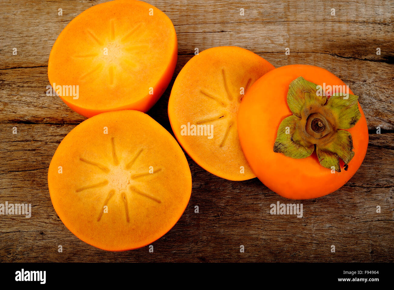 persimmon fruit on wooden background - Stock Image