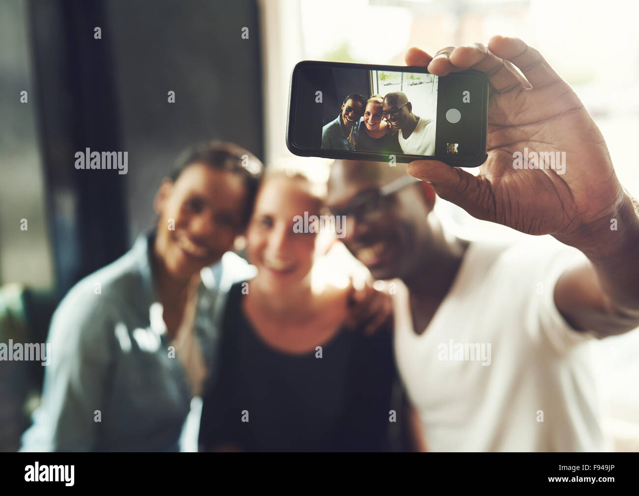 Multi ethnic friends taking a selfie with a phone Stock Photo