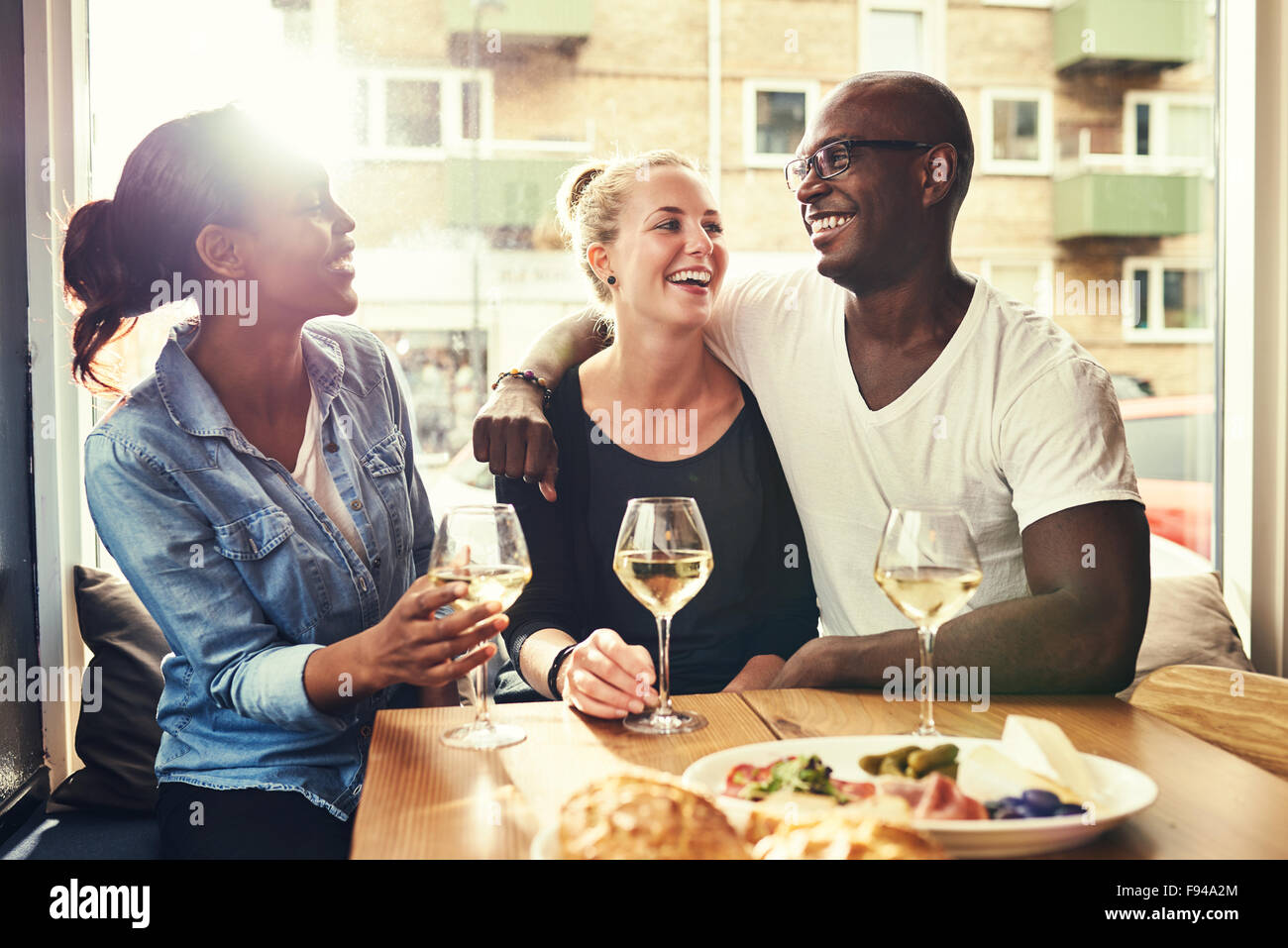 Multi racial couple out dining with a afro american female friend - Stock Image
