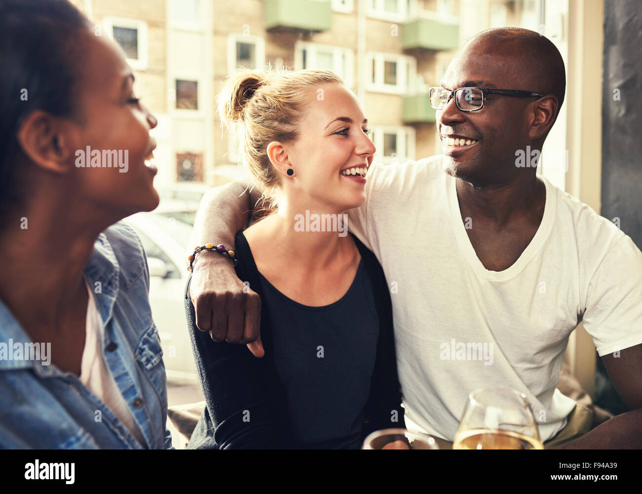 Multi ethnic couple smiling at each other - Stock Image