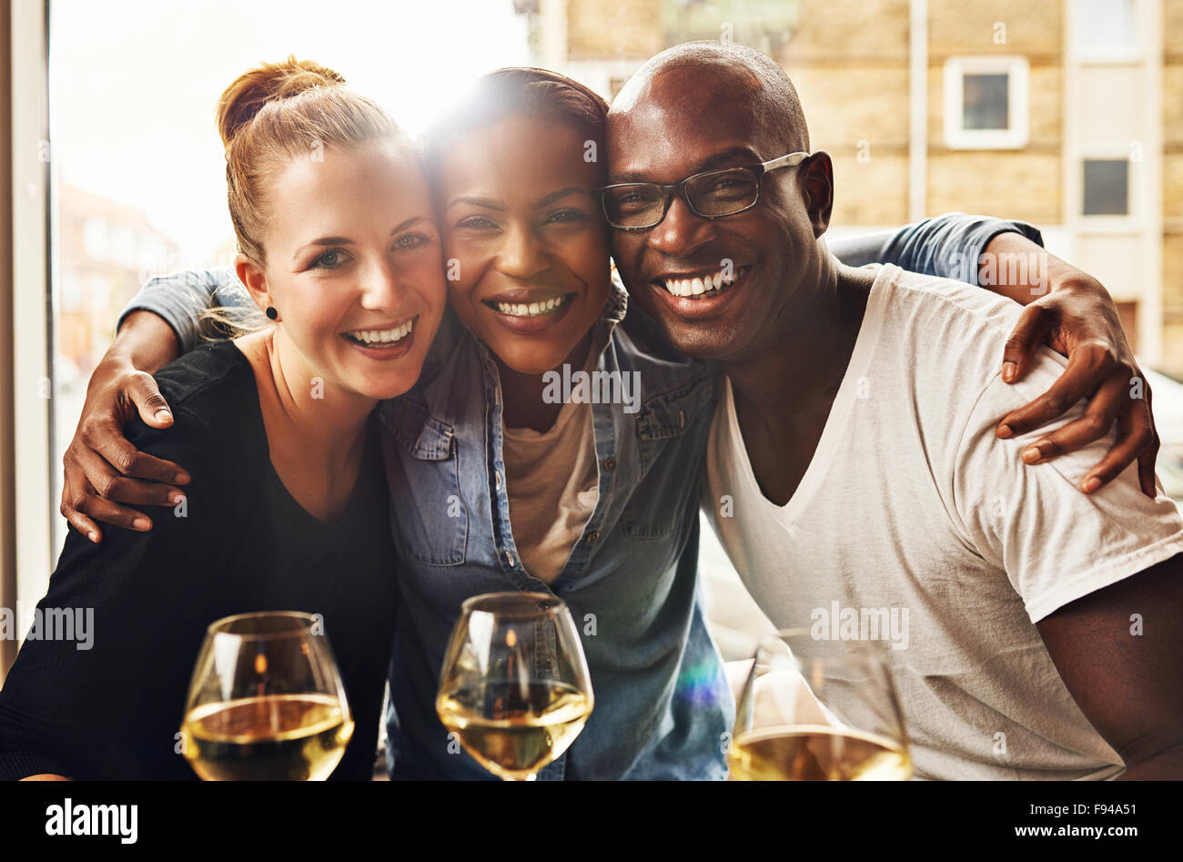 Three ethnic best friends smiling at camera and hugging - Stock Image