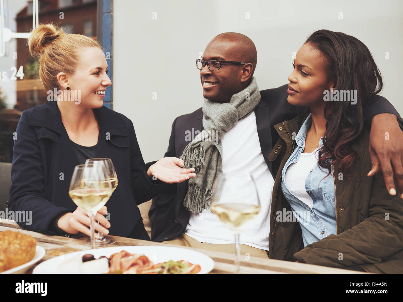 Good friends enjoying dinner outside on a cafe, ethnic friends - Stock Image