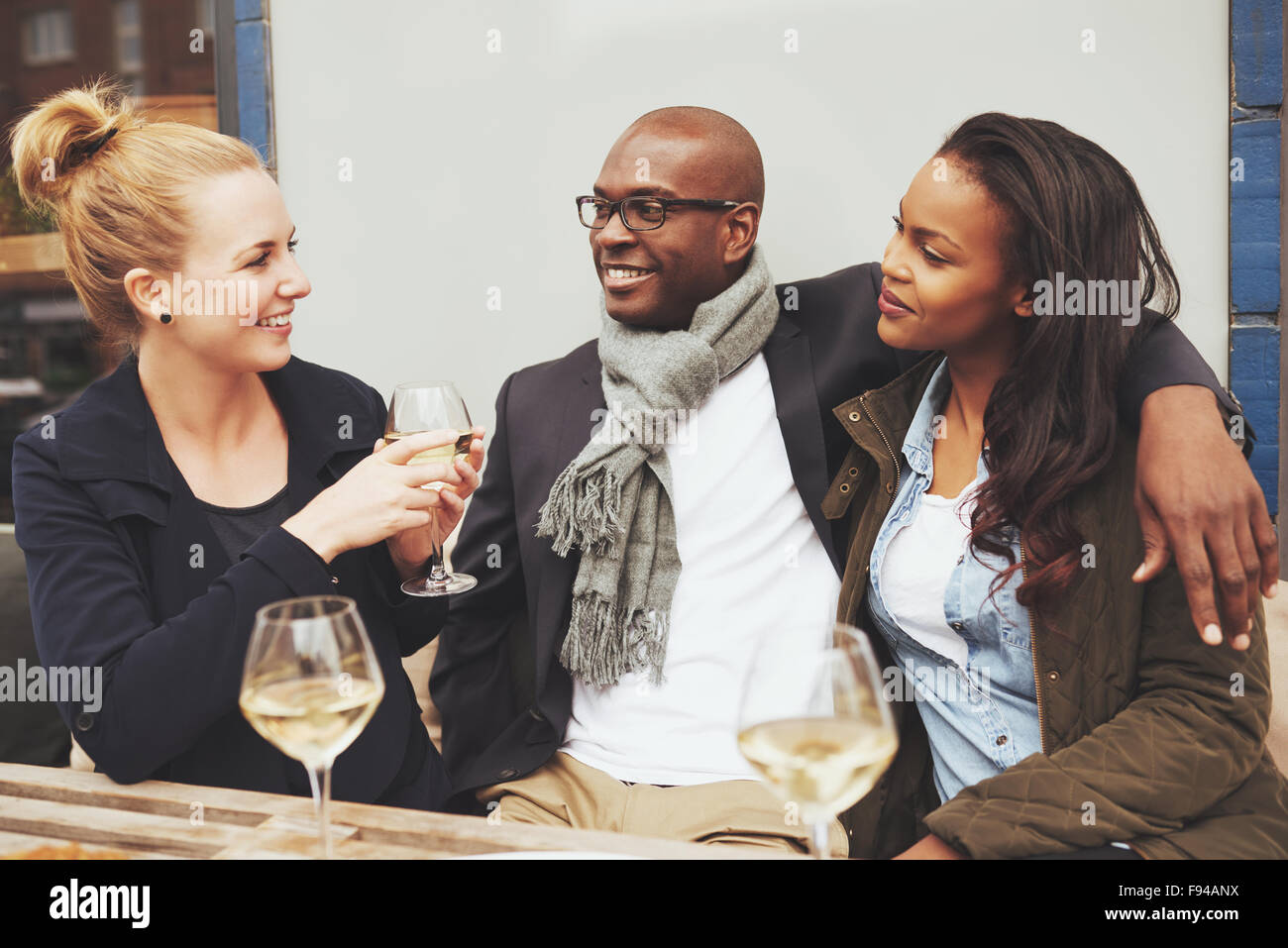 Friends having a conversation at a cafe multi racial friendship - Stock Image