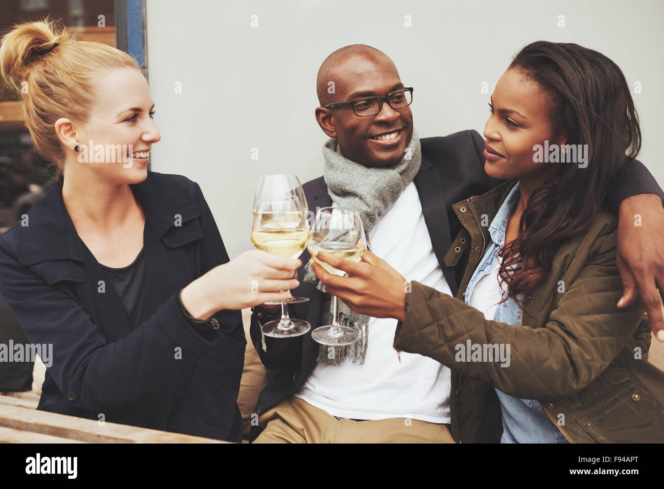 Three multi ethnic friends having a good time on a cafe - Stock Image