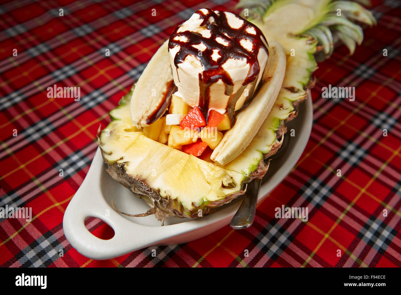 A variation of Banana Split dessert - with fruit salad in-between and ice cream on top, served in pineapple. Krabi - Stock Image