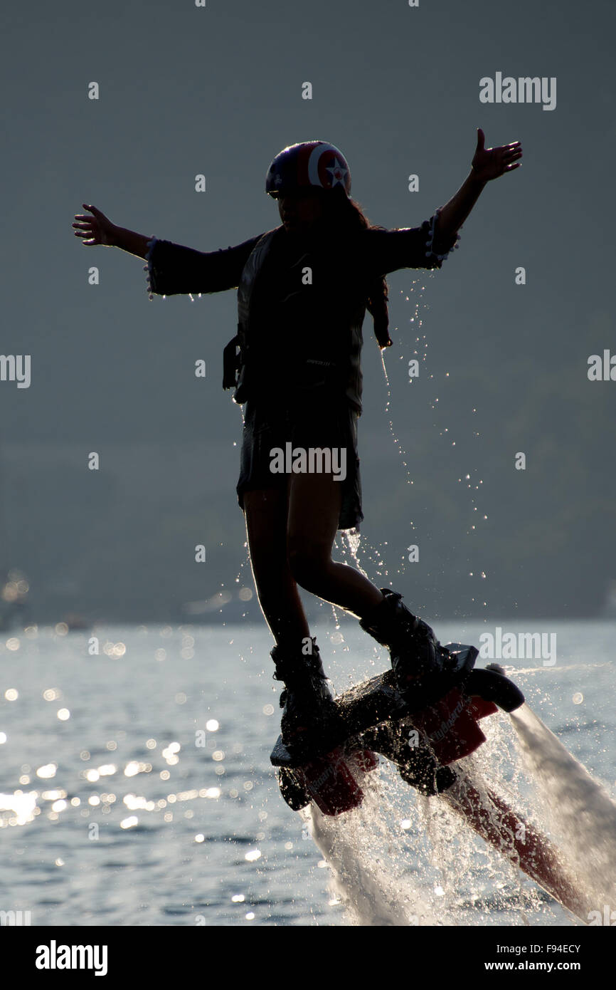Flyboarder with arms outstretched and bent knee - Stock Image