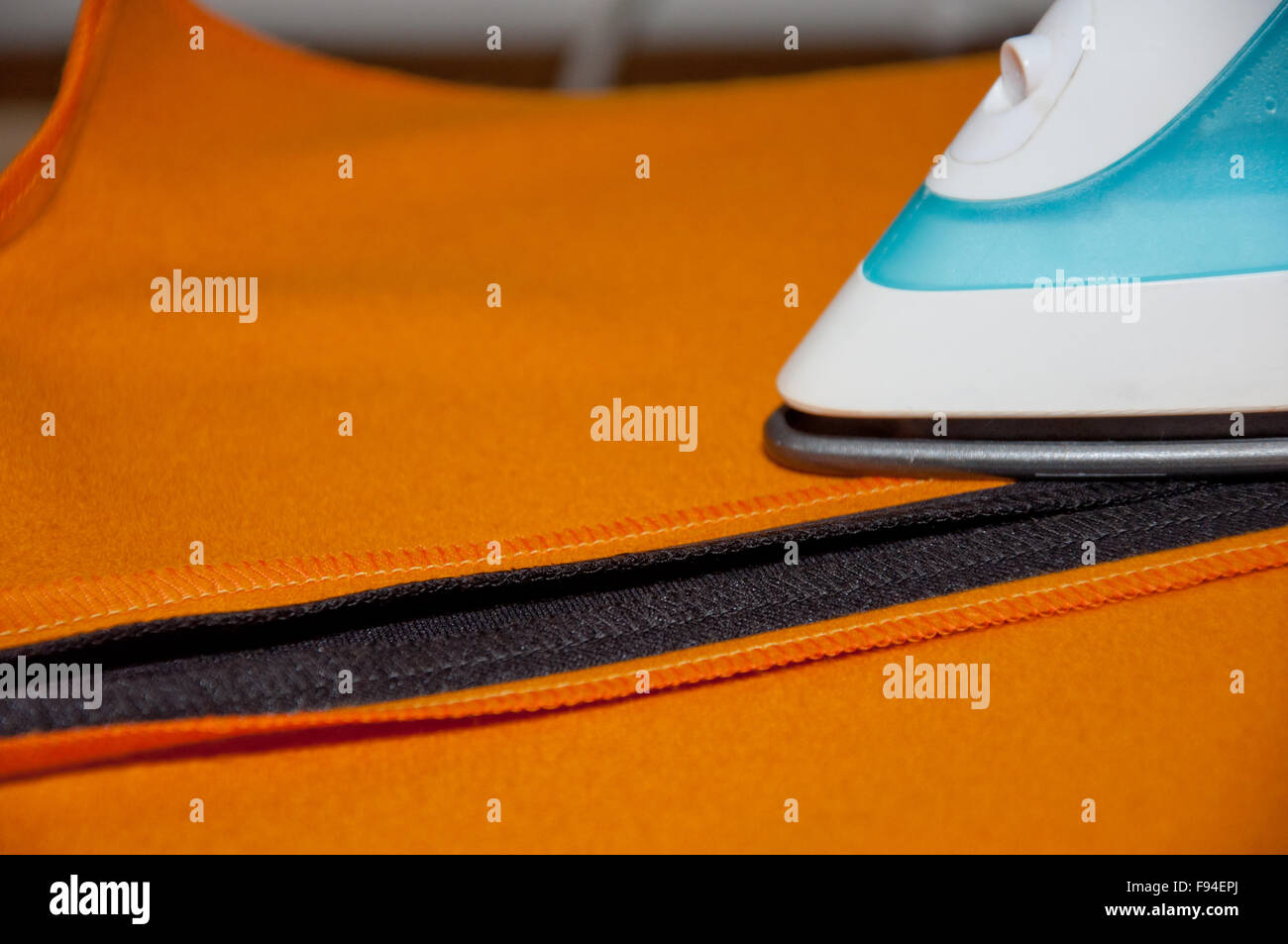 ironing housework orange and black cloth indoors - Stock Image