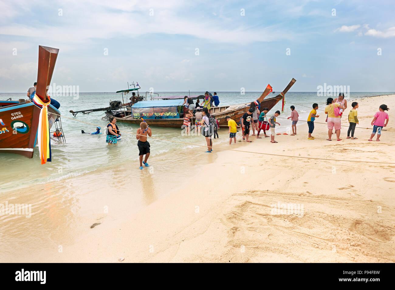Tourists disembark from longtail boat. Poda Island (Koh Poda), Krabi Province, Thailand. - Stock Image