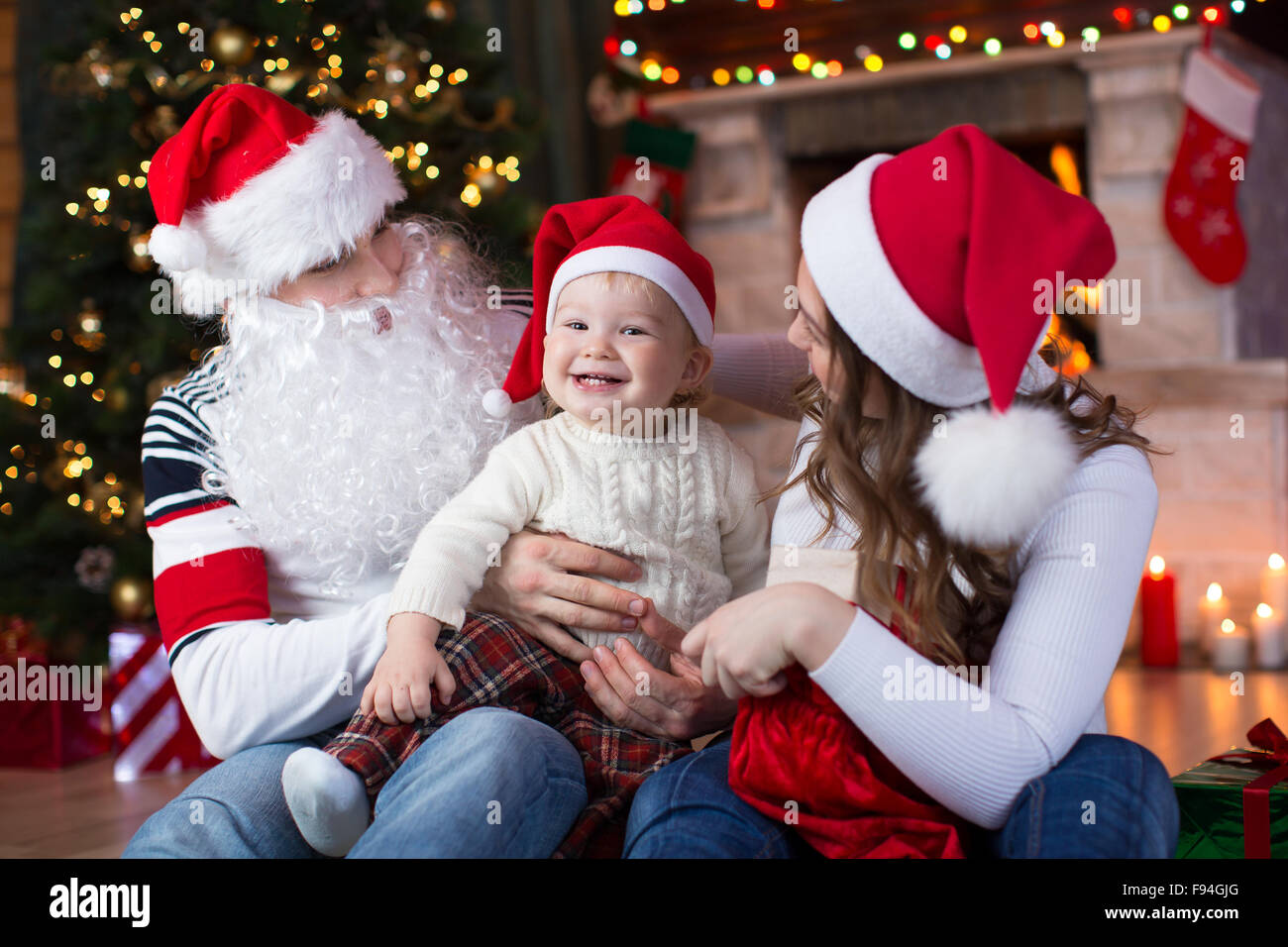 Happy family with child son having a fun near Christmas tree and fireplace  in living room - Stock Image