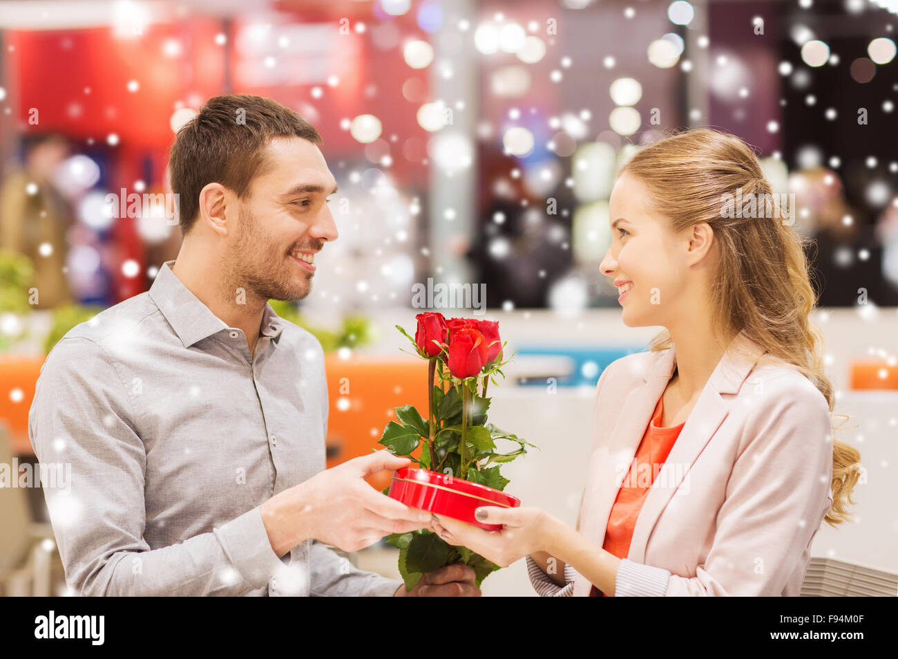 happy couple with present and flowers in mall Stock Photo