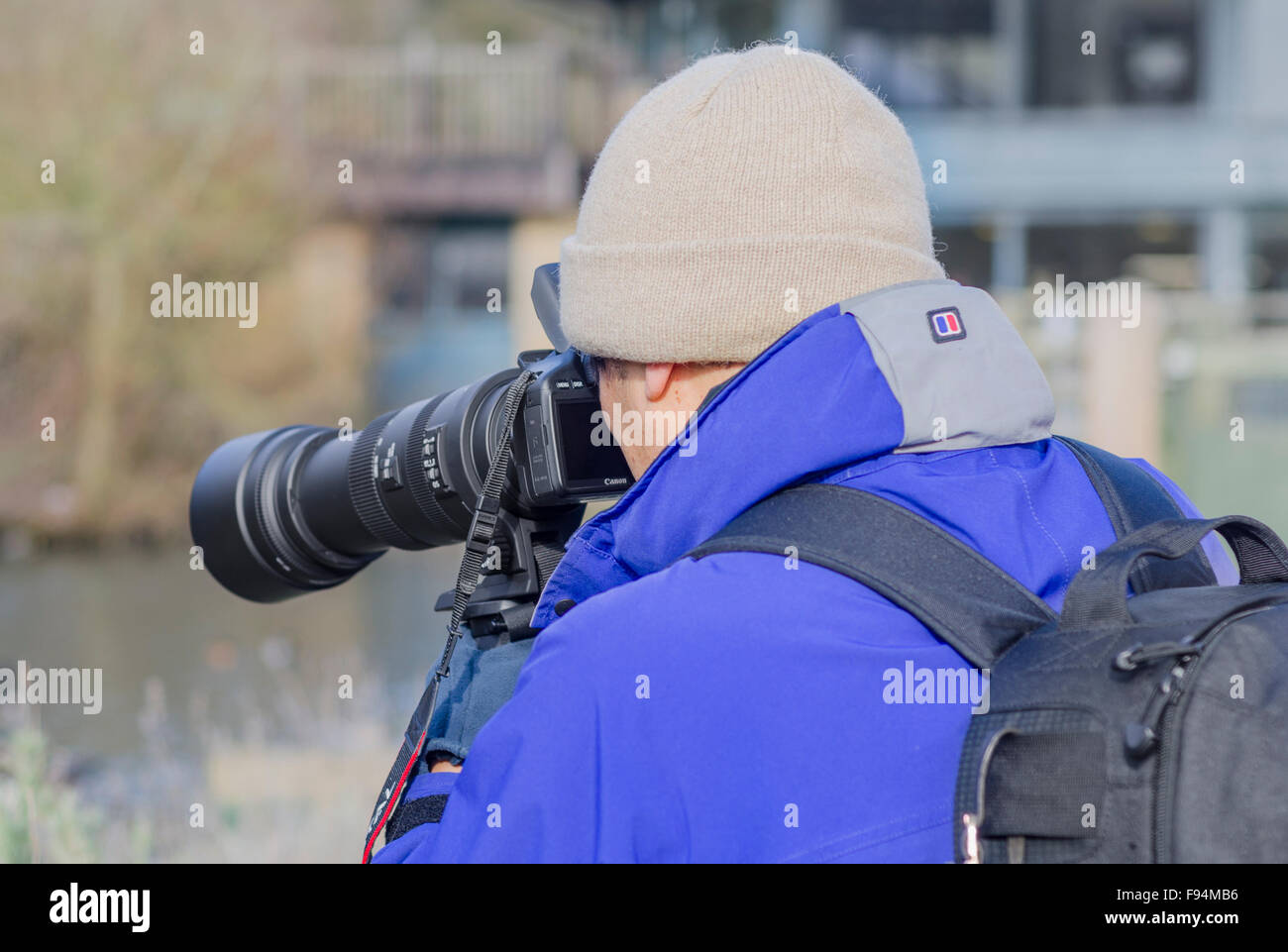 Male photographer with a long telephoto lens. - Stock Image