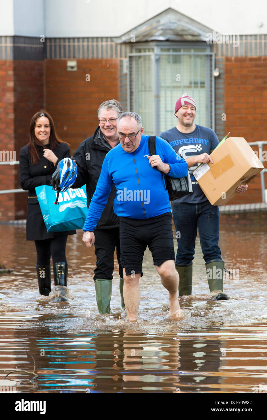 The irony of the t shirt. Carlisle Rugby Club members wade through the flood waters in Carlisle, Cumbria on Tuesday - Stock Image