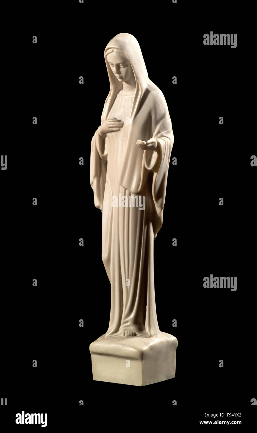 Statue of the Virgin Mary on a black background depicting humility and charity - Stock Image
